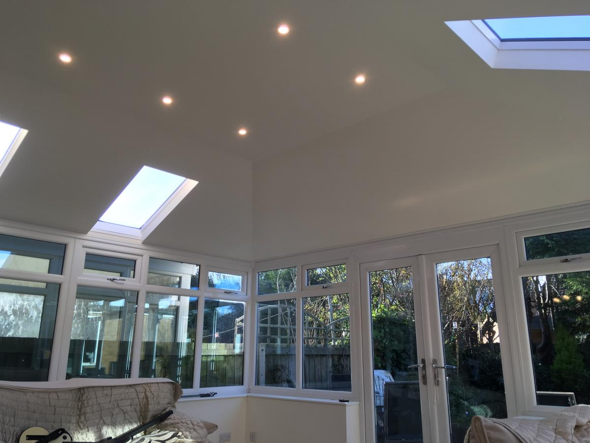 Inside view of a conservatory roof conversion with velux windows and LED lights.