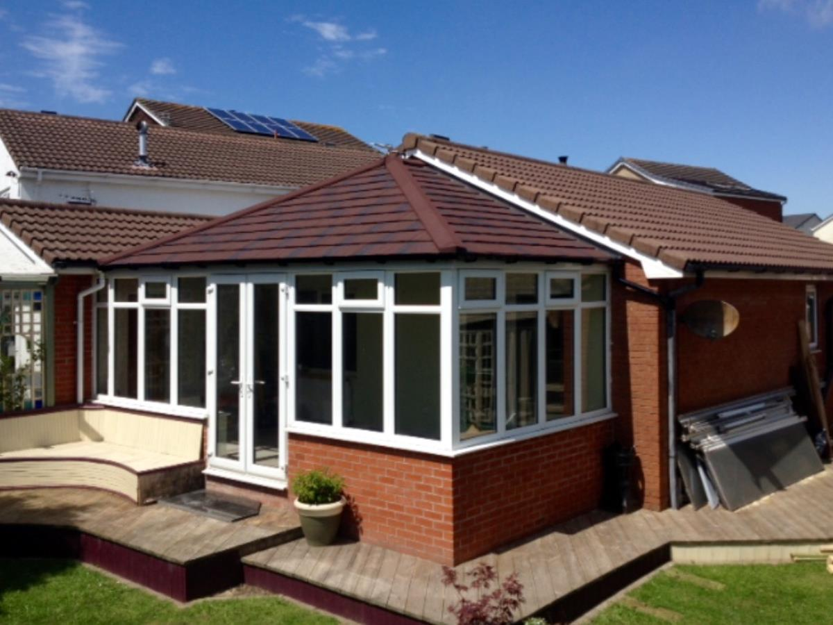 Burnt umber Georgian conservatory solid roof conversion to match roof-line of existing Lytham St Annes property.